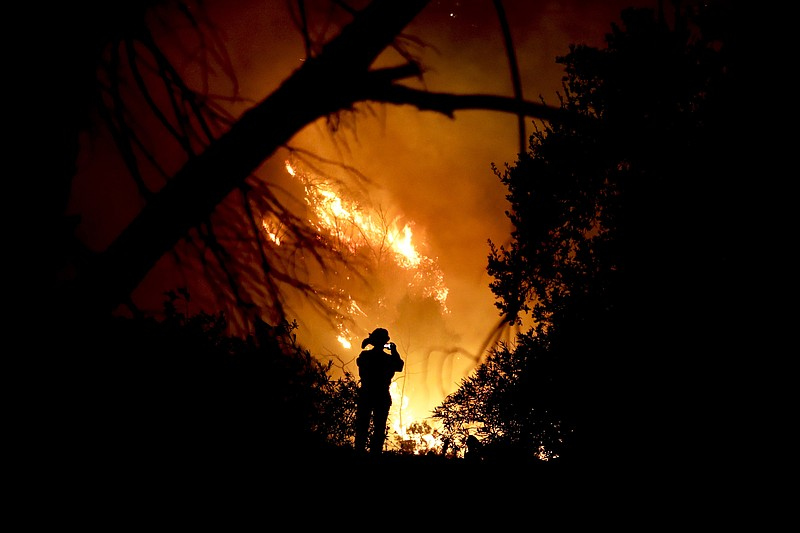 A firefighter takes a cell phone picture during a wildfire in Montecito, Cali...