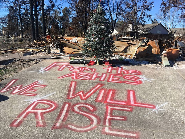 A Christmas tree stands in front of a home destroyed by O...