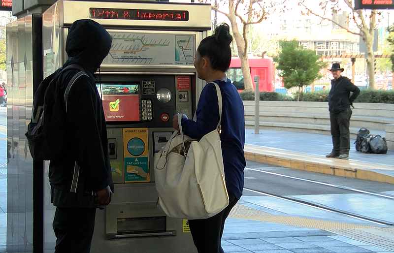 Two transit riders stand in front of a ticket vending machine at the 12th and...