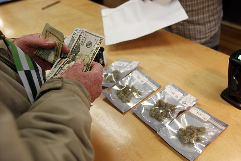 A customer purchases marijuana at Harborside marijuana dispensary, Monday, Ja...