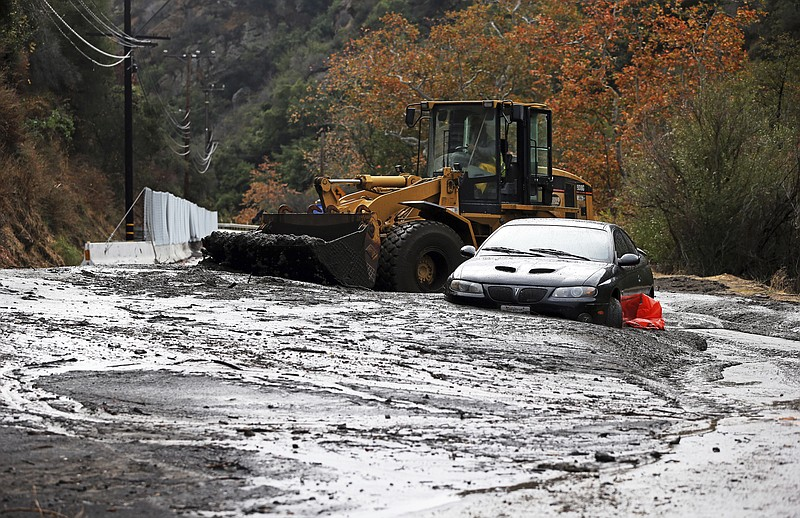 A bulldozer operator begins to clear a car trapped in a deep debris flow that...