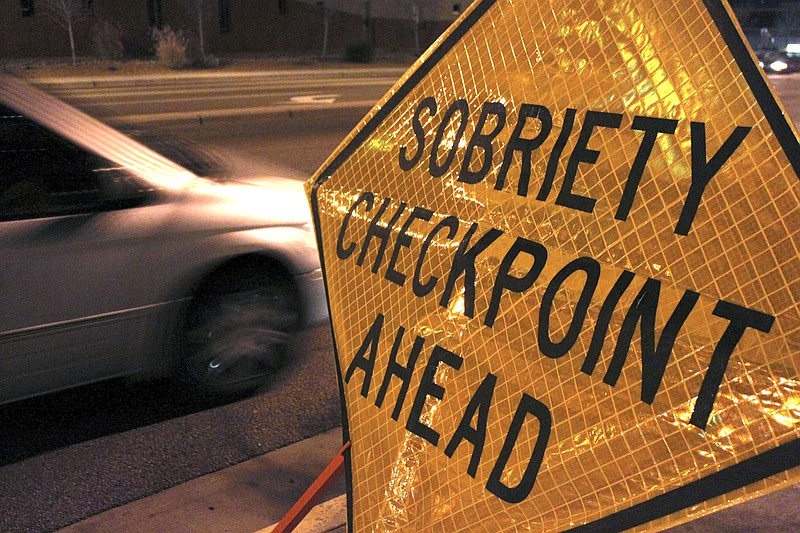 A car approaches a sobriety checkpoint set up along a busy street in Albuquer...