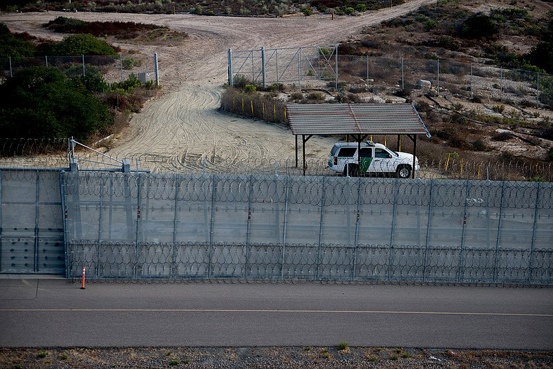 A Border Patrol agent vehicle sits between secondary fencing, which includes ...