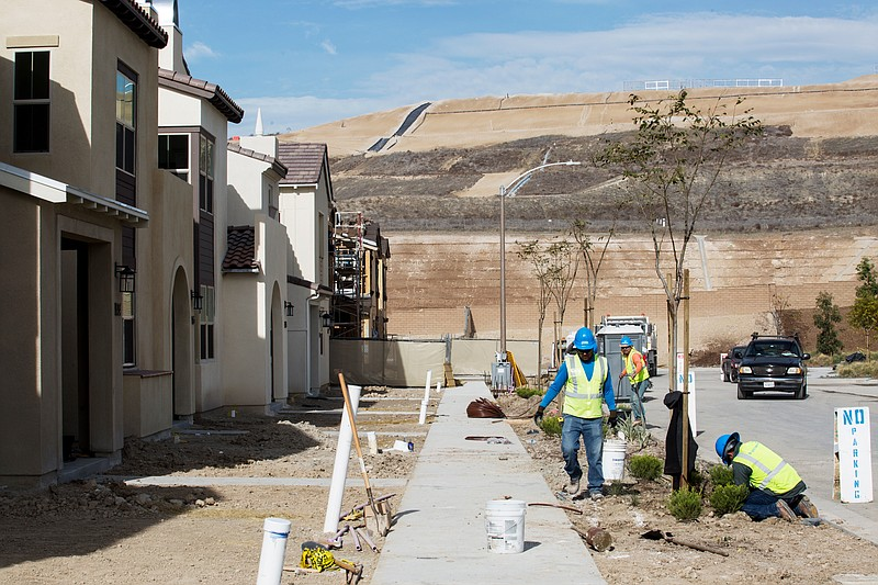 Workers plant vegetation outside new homes in the Otay Ranch Village of Escay...