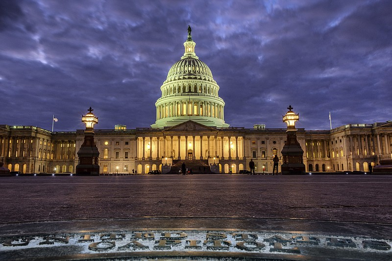 Lights shine inside the U.S. Capitol Building as night falls in Washington, S...