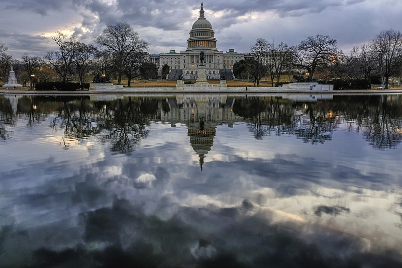 Clouds are reflected in the U.S. Capitol reflecting pool at daybreak in Washi...