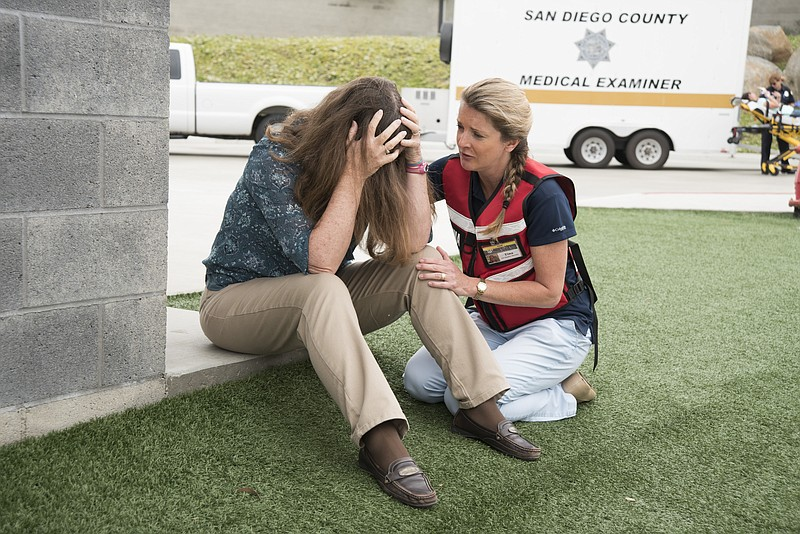 A TIP volunteer comforts a trauma survivor in this undated photo.