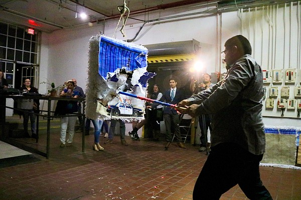 A San Diego resident breaks a piñata of one of the border...