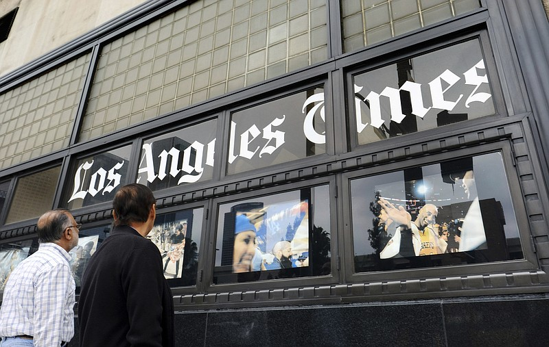 Pedestrians look at news photos posted outside the Los Angeles Times building...