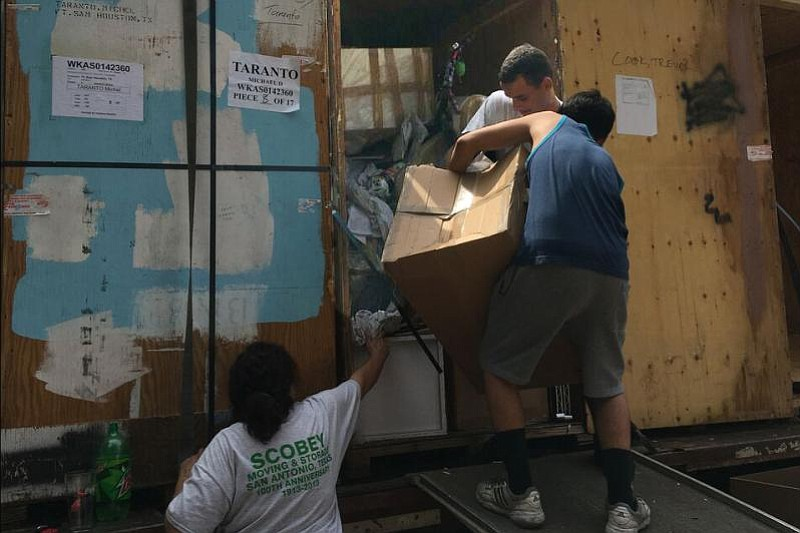Movers unpack a van at Sarah Taranto's house in May 2017. Many of the Taranto...