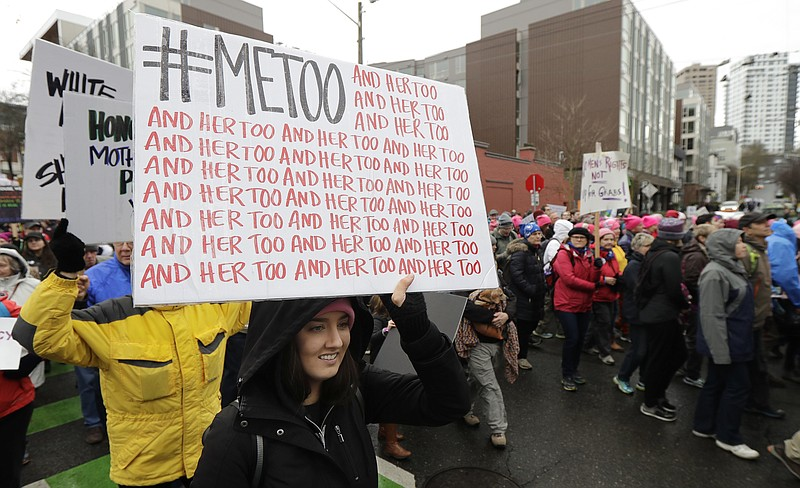 A marcher carries a sign with the popular Twitter hashtag #MeToo used by peop...