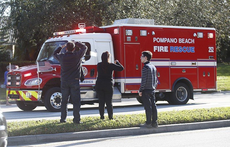 Anxious family members watch a rescue vehicle pass by in Parkland, Fla, Wedne...
