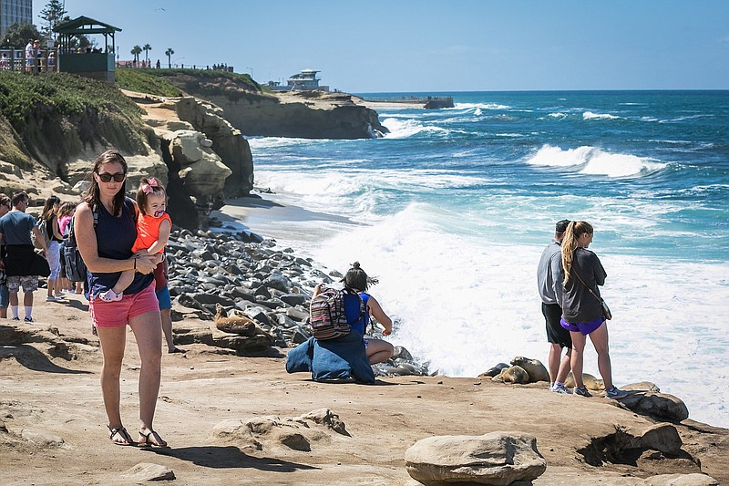Lisa Henry with her daughter Shae walk along a beach in San Diego in this und...