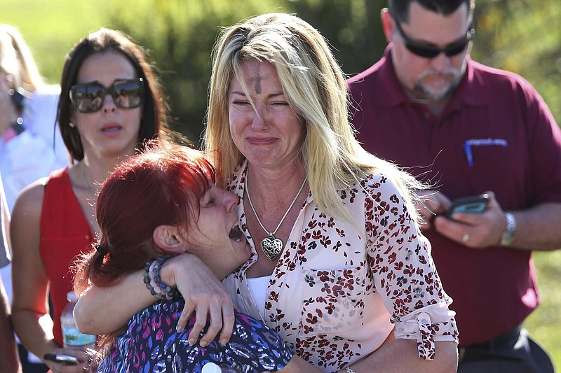 Parents wait for news after a reports of a shooting at Marjory Stoneman Dougl...