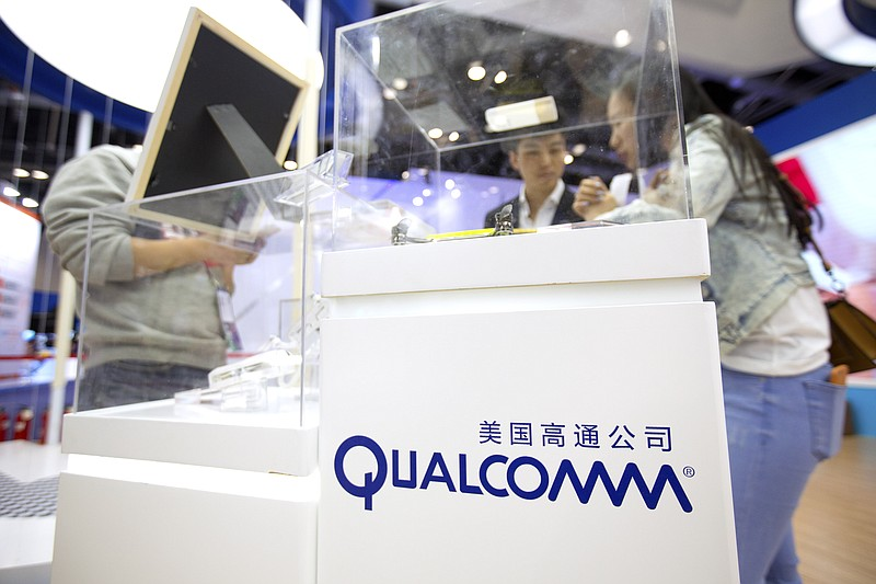 Visitors look at a display booth for Qualcomm at the Global Mobile Internet C...