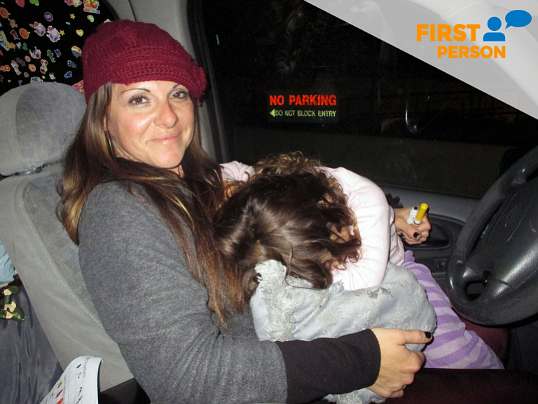 Lola Cheatham is holding her 3-year-old daughter after she fell asleep in her...