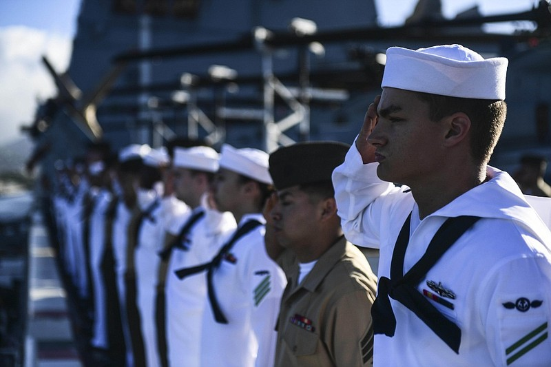 Sailors and Marines render honors on the flight deck of the amphibious transp...