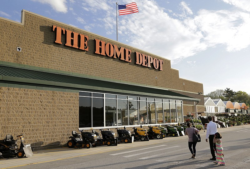 In this May 18, 2016, file photo, people approach an entrance to a Home Depot...