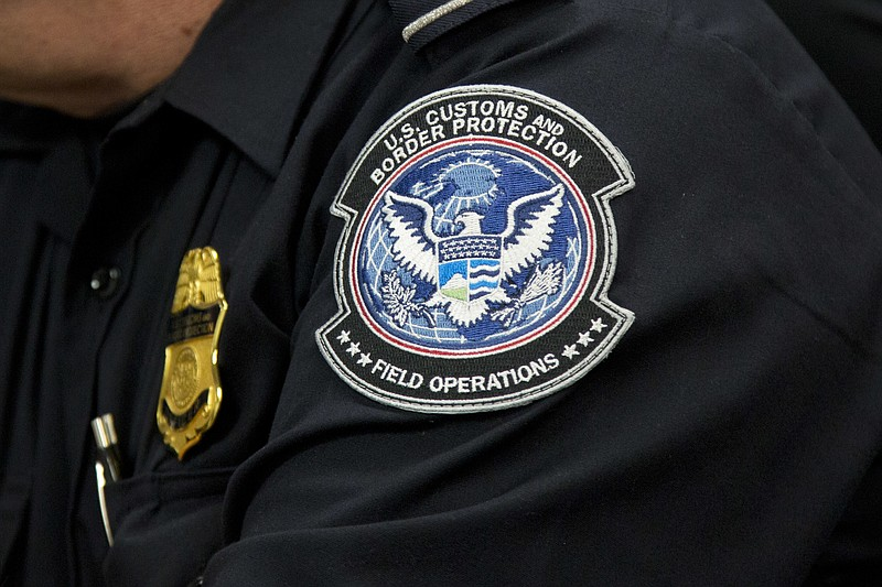 A customs agent wears a patch for the U.S. Customs and Border Protection agen...