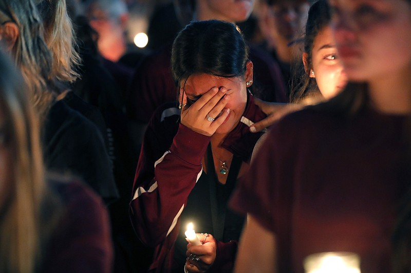 A woman cries during a candlelight vigil for the victims of the Wednesday sho...