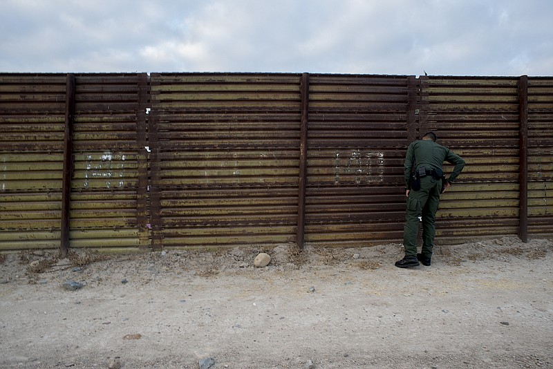 Eduardo Olmos, a Border Patrol public affairs officer, peers through a sectio...
