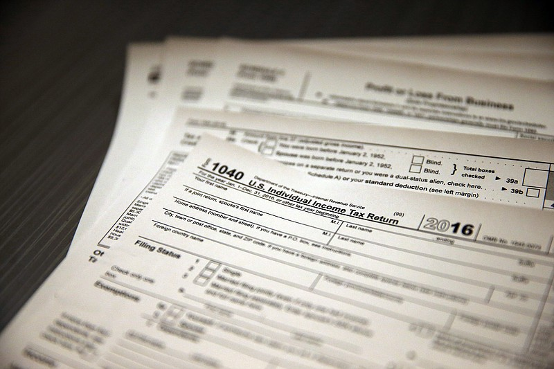 Tax forms sit on a desk at the start of the tax season rush, inside the offic...