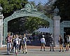 Students walk past Sather Gate on the Universit...
