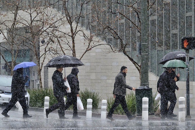 Pedestrians make their way along a street in the pouring rain in downtown Los...