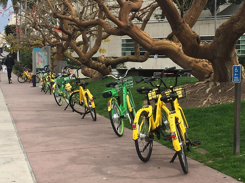 A row of dockless bike-sharing bicycles are parked on a sidewalk in downtown ...