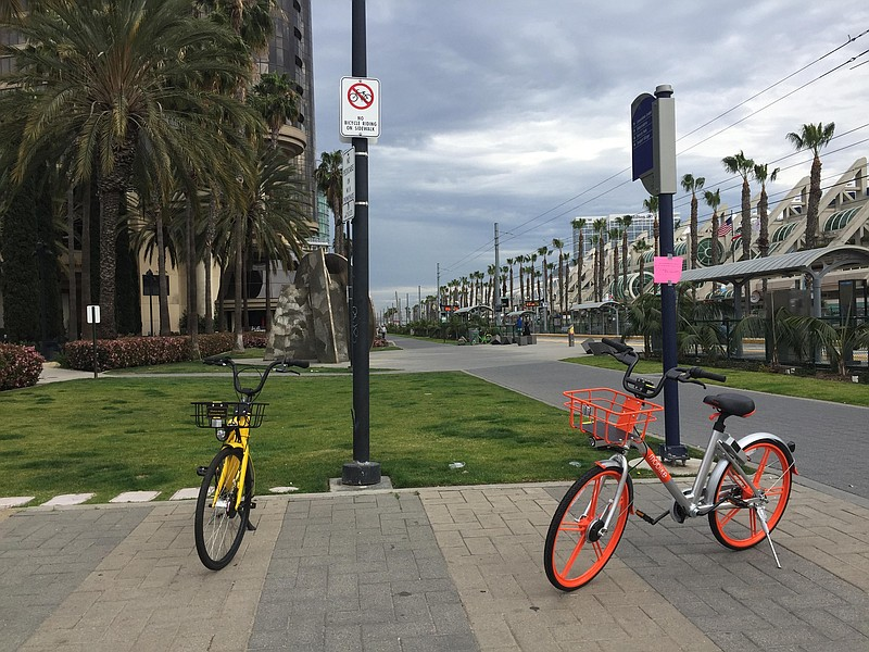A couple of dockless bike-sharing bicycles are parked by the trolley station ...