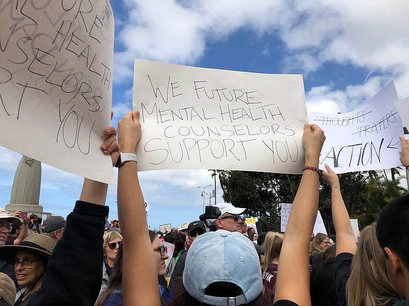 """Demonstrators hold signs at the """"March For Our ..."""