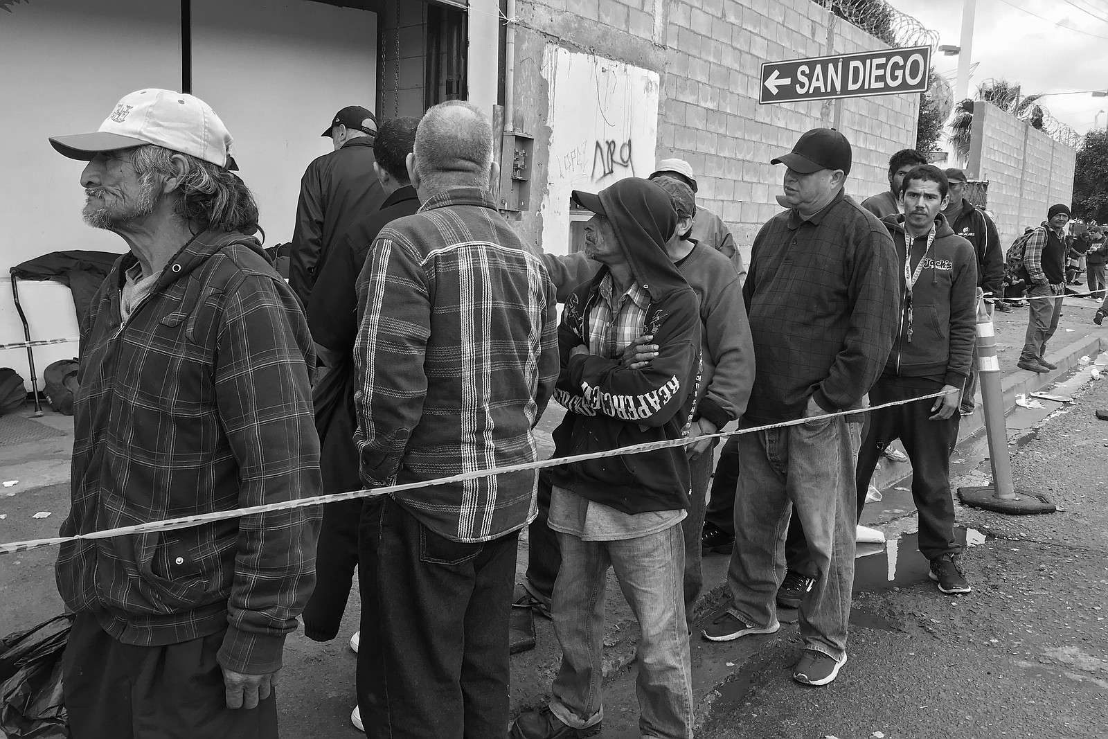 Homeless migrants stand in line for breakfast at Tijuana migrant shelter Desa...