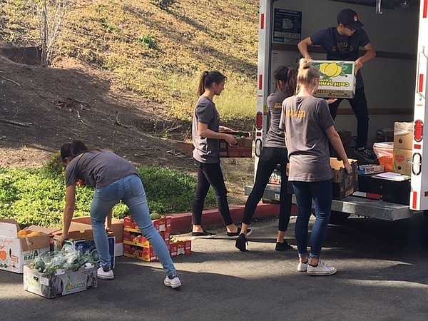 Brightside Produce student team members load a truck with...