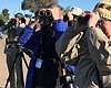 A group of birders on a tour look through binoc...