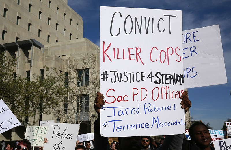 Protestors march down a street block an after the funeral for police shooting...