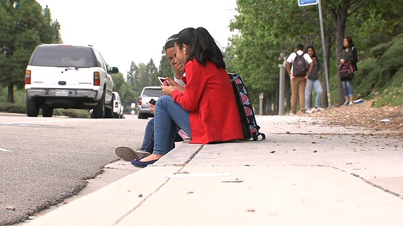 Two Roosevelt Middle School students wait for a North County Transit District...