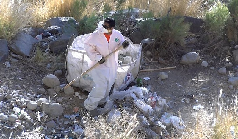 A San Diego city worker cleans up trash along the San Diego River, Dec. 13, 2...