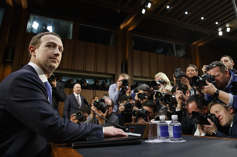 Facebook CEO Mark Zuckerberg takes a seat as he arrives to testify before a j...