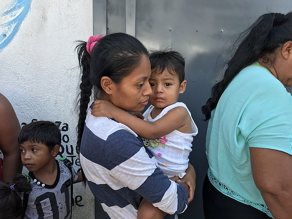 An asylum seeking mother holds her child in Tijuana, Apri...