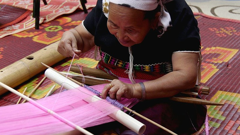 Nya Paw demonstrates the traditional Karen art of weaving on a bamboo loom at...