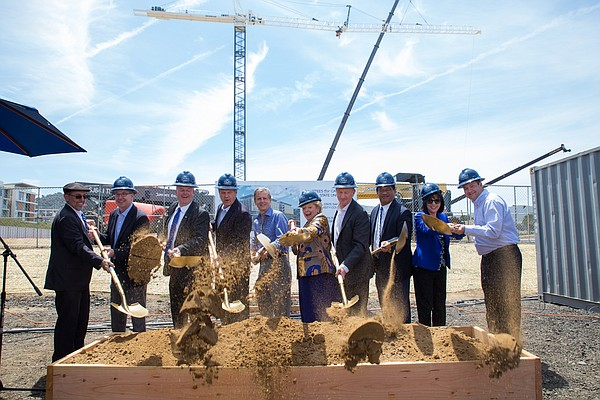 Dignitaries toss the first shovel of dirt at the groundbr...