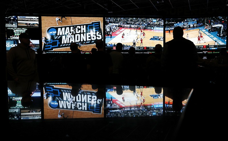 People watch coverage of the first round of the NCAA college basketball tourn...