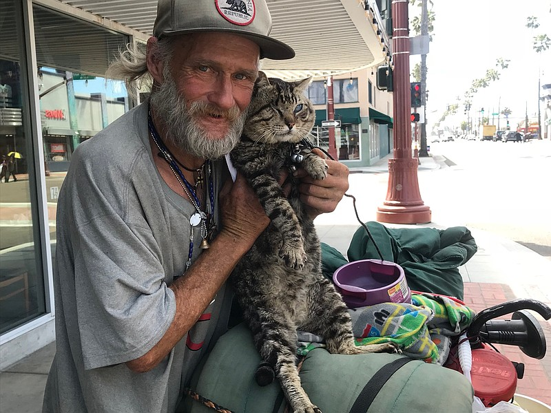 Robert Glen, who is homeless in Oceanside, poses for a photo with Peanut, his...
