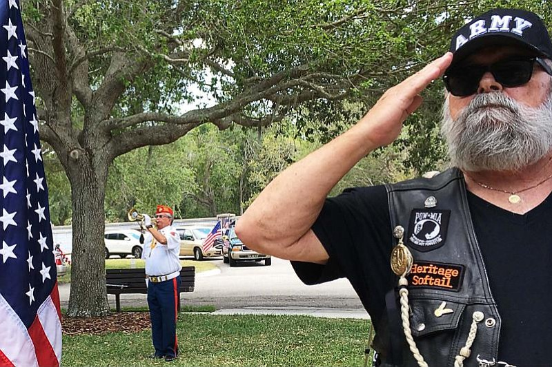 A bugler plays Taps at Bay Pines National Cemetery as veterans stand at atten...
