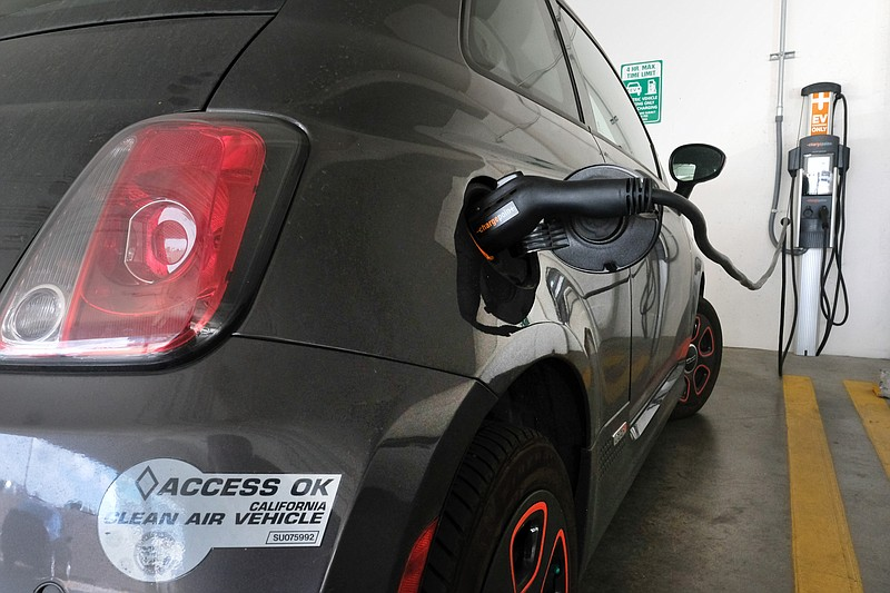 This April 25, 2016 file photo shows an electric Fiat plugged into a charging...
