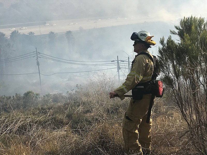 A firefighter looks onto smoke from a brush fire along I-8, June 3, 2018.