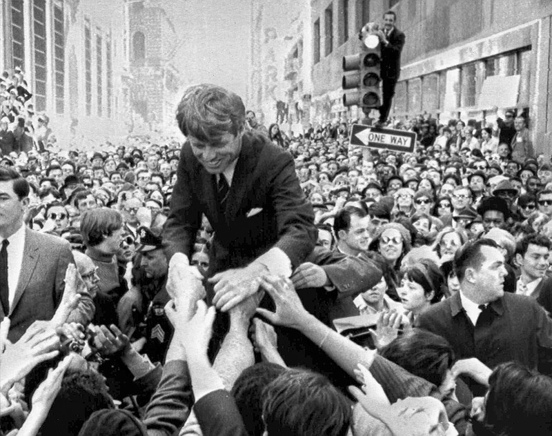 U.S. Sen. Robert F. Kennedy, D-NY, shakes hands with people in a crowd while ...
