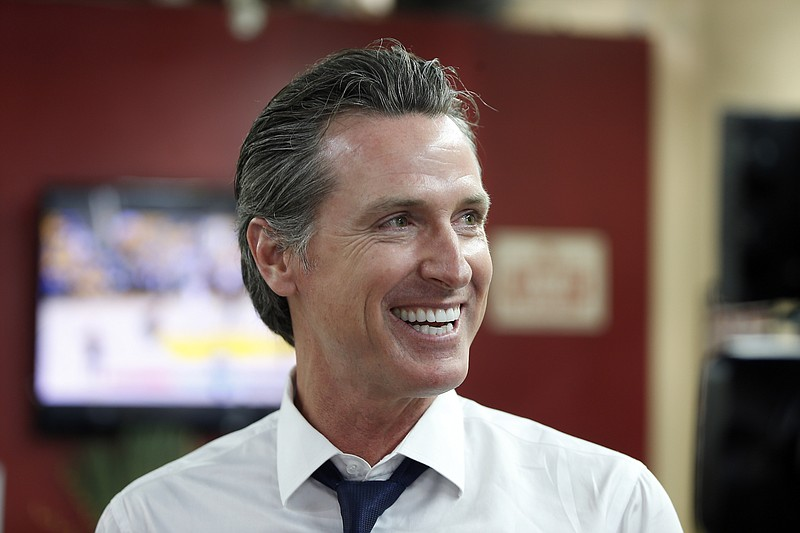 Democratic Lt. Gov. Gavin Newsom smiles at a campaign stop at Stakely's Barb...