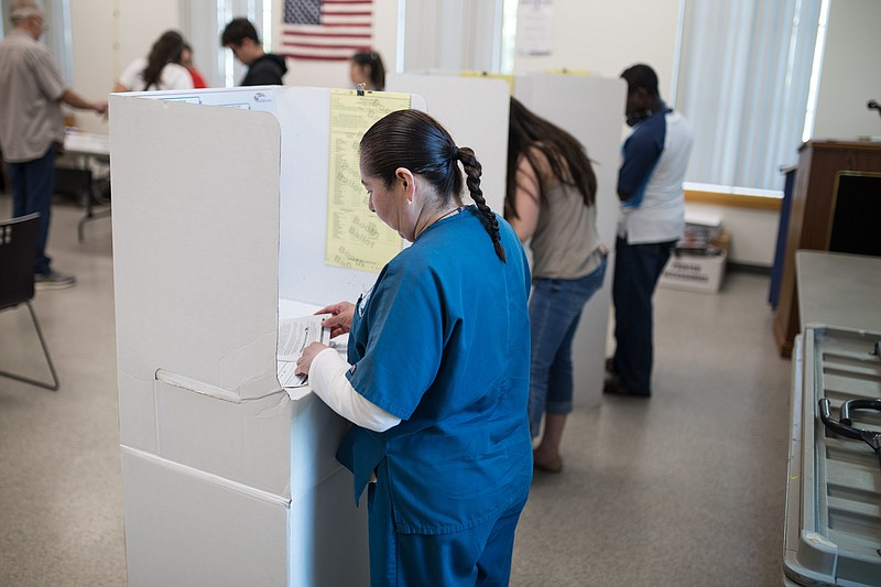 Voters are shown casting ballots at the City Heights/Weingart Library on June...