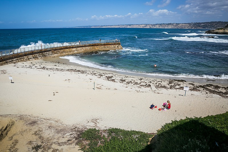 A family sits on the sand at Children's Pool Beach in La Jolla, CA in this un...